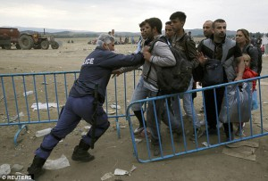 A_policeman_pushes_refugees
